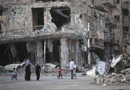 People walk along a damaged street filled with debris in Deir al-Zor