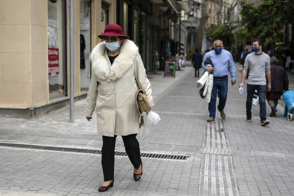 A woman wearing a hat and a protective face mask walk in central Athens, on Monday, April 5, 2021. Retail stores across most of Greece have been allowed to reopen despite an ongoing surge in COVID-19 infections, as the country battled to emerge from deep recession.(AP Photo/Petros Giannakouris)