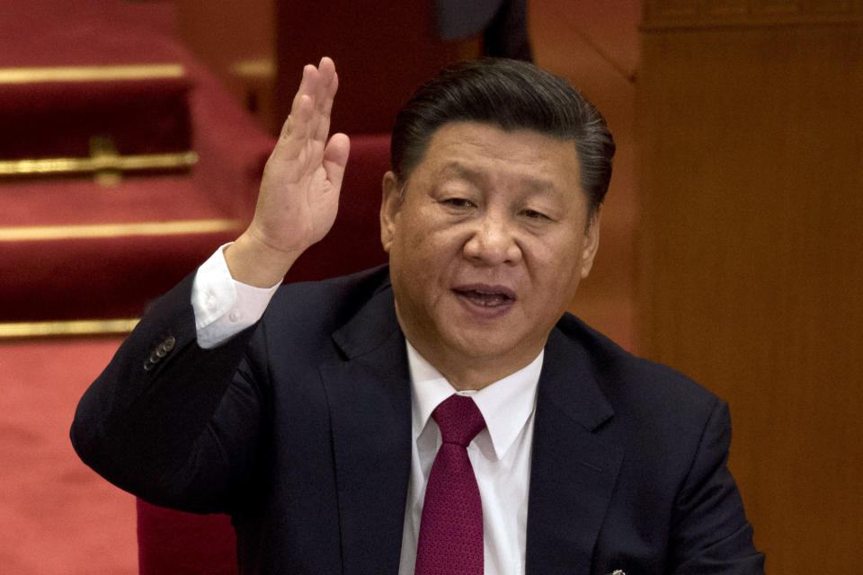 FILE - In this Oct. 24, 2017, file photo, Chinese President Xi Jinping raises his hand to show approval of a work report during the closing ceremony for the 19th Party Congress at the Great Hall of the People in Beijing, China. A spate of recent Chinese military flights off Taiwan, which Beijing claims as its own, and naval maneuvers by the United States and its allies to reinforce maritime routes challenged by China are fueling increasing tensions in a region already on edge. (AP Photo/Ng Han Guan, File)