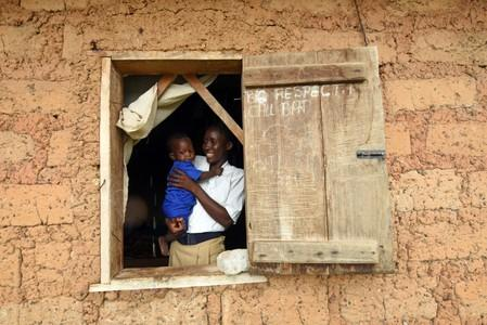 Mariatu Sesay, 15, carries her daughter as she looks out the window in a countryside village of Sierra Leone