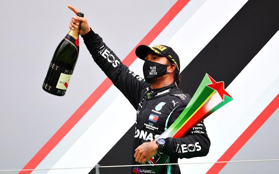 Race winner Lewis Hamilton of Great Britain and Mercedes GP celebrates his record breaking 92nd race win on the podium during the F1 Grand Prix of Portugal at Autodromo Internacional do Algarve on October 25, 2020 in Portimao, Portugal. - Bryn Lennon/Formula 1