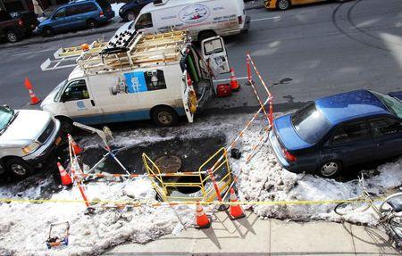 A Consolidated Edison van is parked near a manhole surrounded by cones and safety barriers on 116th Street in  New York