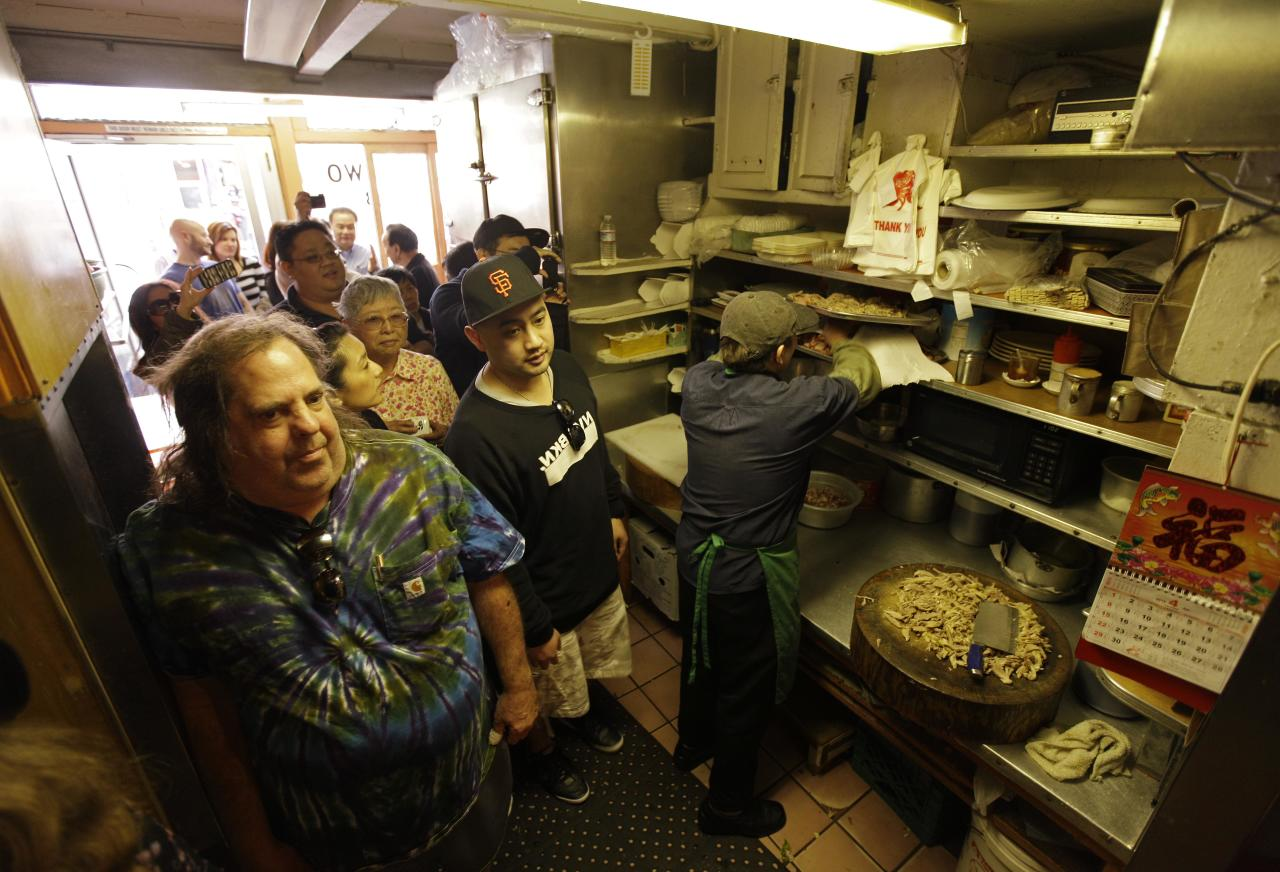 """Sam Begler, left, and other customers wait in the kitchen for a table at the Sam Wo restaurant in Chinatown in San Francisco, Friday, April 20, 2012. The 100-year-old Chinese restaurant known for having """"the world's rudest waiter"""" is shutting its doors and serving its last customers Friday. (AP Photo/Eric Risberg)"""