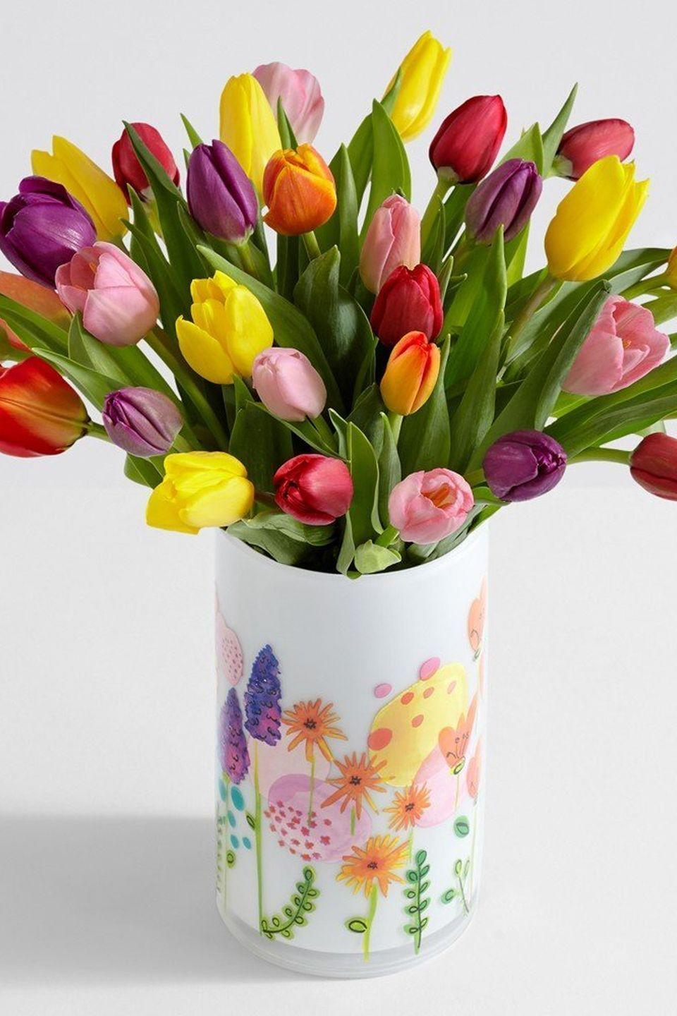 """<p>If your position for your tablescape is the more color, the better, this vase of five different shades of tulips will blend right in.</p><p><strong><em>Vintage Lavender Frosted Fenton Vase,</em></strong> <strong><em>$45</em></strong> <a class=""""link rapid-noclick-resp"""" href=""""https://go.redirectingat.com?id=74968X1596630&url=https%3A%2F%2Fwww.etsy.com%2Flisting%2F702862015%2Fvintage-lavender-satin-glass-vase&sref=https%3A%2F%2Fwww.housebeautiful.com%2Fentertaining%2Fflower-arrangements%2Fg19409803%2Feaster-flower-arrangements%2F"""" rel=""""nofollow noopener"""" target=""""_blank"""" data-ylk=""""slk:BUY NOW"""">BUY NOW</a></p>"""