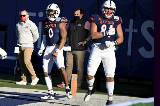 UTSA quarterback Frank Harris (0) celebrates his rushing touchdown with teammate Oscar Cardenas (84) in the second quarter during the SERVPRO First Responders Bowl NCAA college football game against Louisiana in Dallas, Saturday, Dec. 26, 2020. (AP Photo/Matt Strasen)