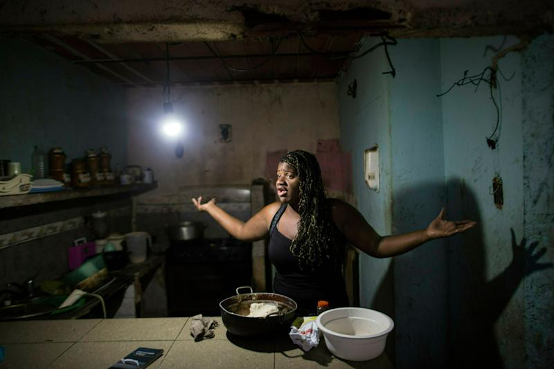 """In this Feb. 14, 2019 photo, Dugleidi Salcedo complains to a neighbor about the high price of food as she prepares arepas for her three sons in her kitchen in the Petare slum, in Caracas, Venezuela. Hunger drove Salcedo to send her four-year-old daughter to live with an aunt when she could no longer feed her. """"My boys cry,"""" the single mother of four said. """"But they resist more than her when I tell them that there's no food."""" (AP Photo/Rodrigo Abd)"""