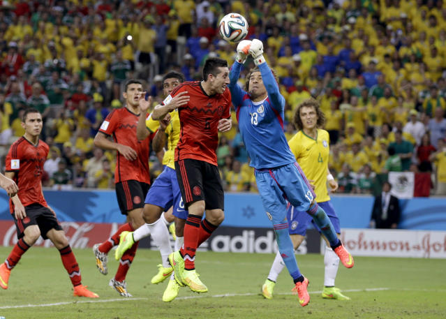 Mexico's goalkeeper Guillermo Ochoa punches the ball clear during the group A World Cup soccer match between Brazil and Mexico at the Arena Castelao in Fortaleza, Brazil, Tuesday, June 17, 2014