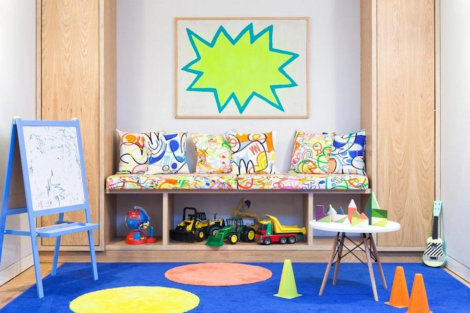 "<p>Since design is bound to be more kid-friendly and fun in a playroom than in other rooms in the home, you can do wilder things, like choose graffiti-print upholstery and neon artwork, like <a href=""http://www.2lgstudio.com/"" rel=""nofollow noopener"" target=""_blank"" data-ylk=""slk:2LG Studio"" class=""link rapid-noclick-resp"">2LG Studio</a> did here. But if there's one thing you need take seriously in the playroom, it's storage. The built-in cabinets and shelves under the bench will keep things tidy and organized. </p>"
