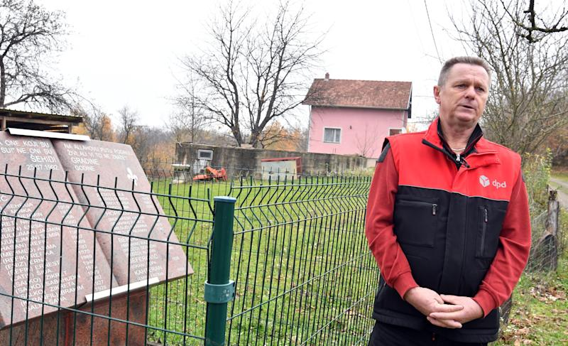 Bosnian Muslim, Fikret Bacic (59), whose wife and 2 children were executed in 1992 by Bosnian-Serb forces, stands next to the stone monument, honoring members of his family murdered on his former homestead in the village of Zecovi, near Prijedor, in Northern Bosnia, on November 20, 2017. Apart from his wife and children, 26 of Bacic's relatives were killed including his brother and his family. Fikret Bacic, to date, remains on a mission to find remains of his beloved ones. United Nations judges on November 22, 2017 sentenced former Bosnian Serbian commander Ratko Mladic to life imprisonment after finding him guilty of genocide and war crimes in the brutal Balkans conflicts over two decades ago. / AFP PHOTO / ELVIS BARUKCIC (Photo credit should read ELVIS BARUKCIC/AFP via Getty Images)