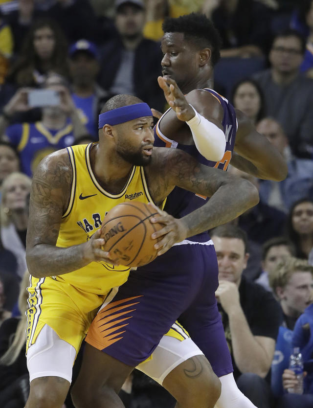 Golden State Warriors center DeMarcus Cousins, left, drives to the basket against Phoenix Suns center Deandre Ayton during the first half of an NBA basketball game in Oakland, Calif., Sunday, March 10, 2019. (AP Photo/Jeff Chiu)