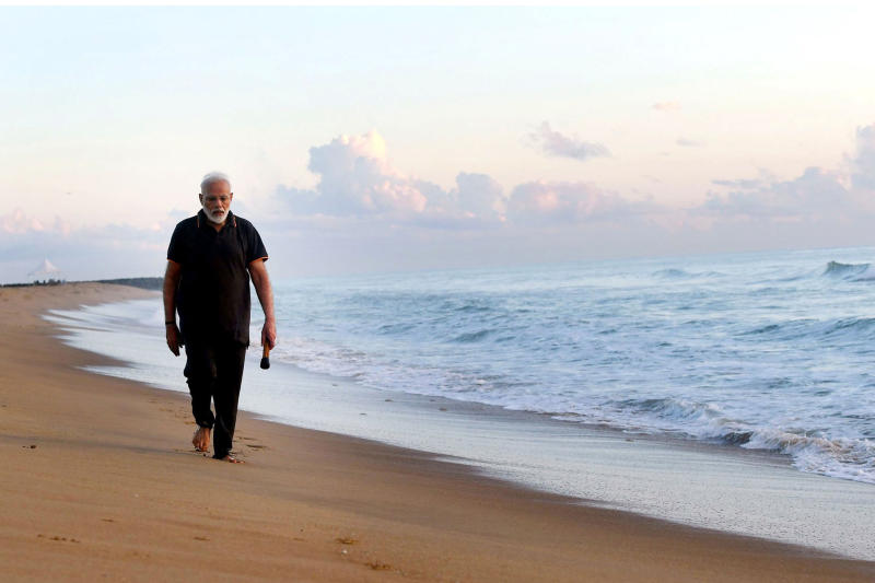 In this photo provided by Prime Minister of India Narendra Modi's twitter handle, Indian Prime Minister Narendra Modi takes morning walk at a beach in Mamallapuram, in southern India, Saturday, Oct. 12, 2019. India's foreign ministry said Chinese President Xi Jinping and Modi met in the seaside temple town of Mamallapuram over dinner for nearly two hours on Friday. The talks will continue Saturday. (Prime Minister of India Narendra Modi's twitter handle via AP Photo)