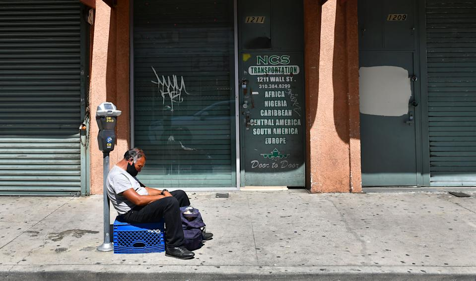 A man sleeps in front of closed shopfronts in what would be a normally busy fashion district in Los Angeles, California on May 4, 2020. - California governor Gavin Newsom earlier today announced the gradual reopening of the state later this week as dismal US employment figures are expected with the release of figures Friday May 8 for April's US jobs report, as 30 million Americans filed for unemployment in the last six weeks. (Photo by Frederic J. BROWN / AFP) (Photo by FREDERIC J. BROWN/AFP via Getty Images)