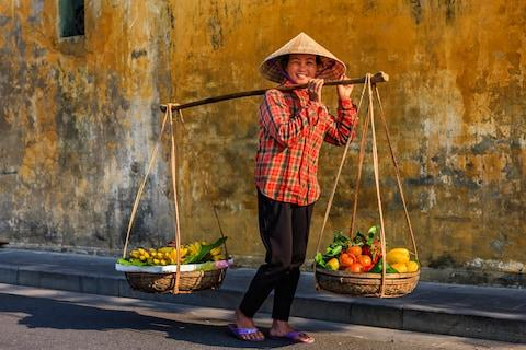 A fruit seller in Hoi An, Vietnam - Credit: GETTY