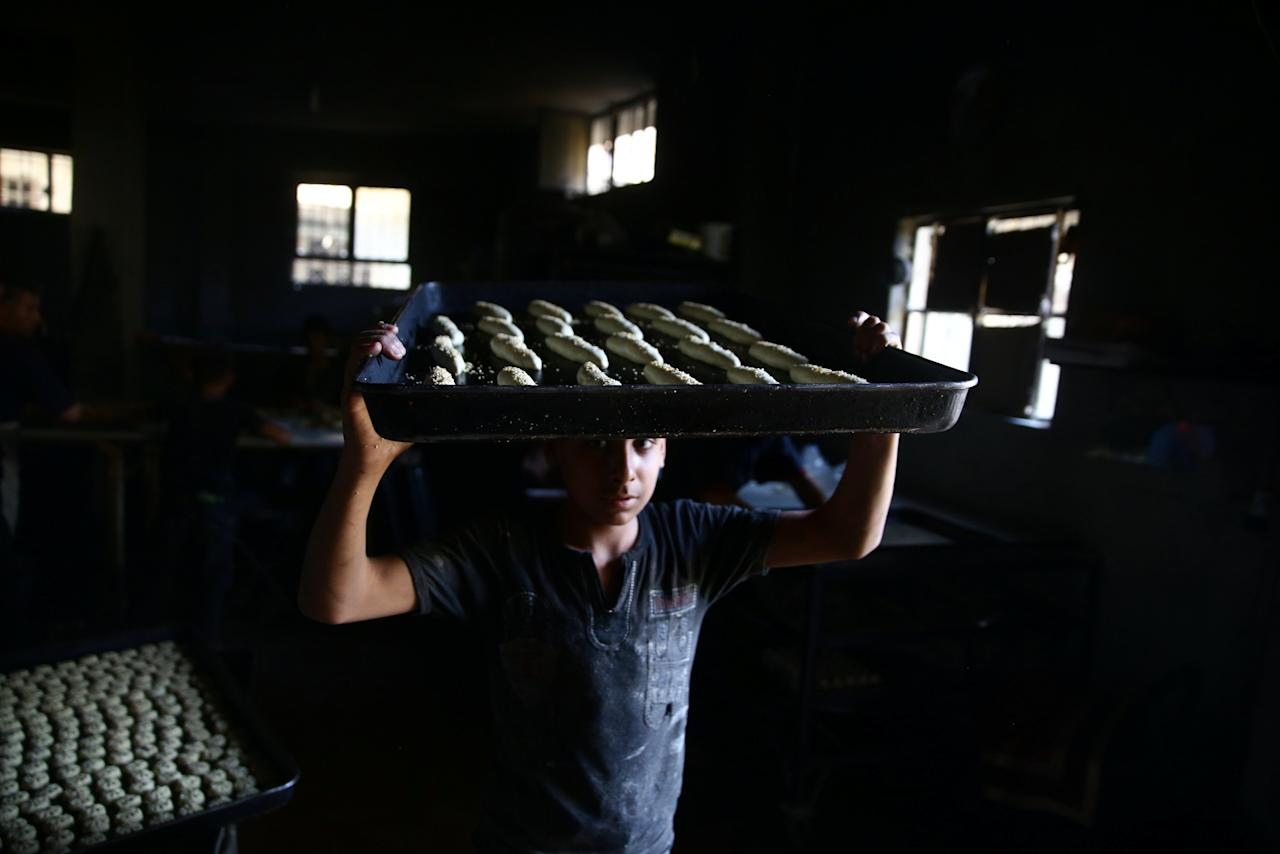 A boy carries raw pastries prior to baking, to be sold during Ramadan in the rebel held besieged eastern Damascus suburb of Ghouta, Syria May 28, 2017. REUTERS/Bassam Khabieh