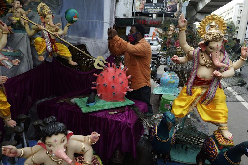 A devotee takes picture of a COVID-19 coronavirus themed elephant headed Hindu god Ganesha idol at a workshop ahead of the Ganesh Chaturthi festival in Hyderabad on August 18, 2020. (Photo by NOAH SEELAM / AFP) (Photo by NOAH SEELAM/AFP via Getty Images)