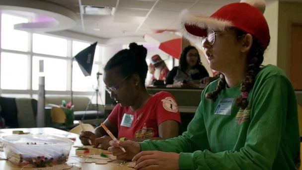 PHOTO: Anna Grace Cornell, 16, and Charlotte Cornell, 14, color pictures with patients at AdventHealth for Children Hospital in Orlando, Fla, during a holiday event with the Surfing Santas. (NPI/Florida's Space Coast Office of Tourism)