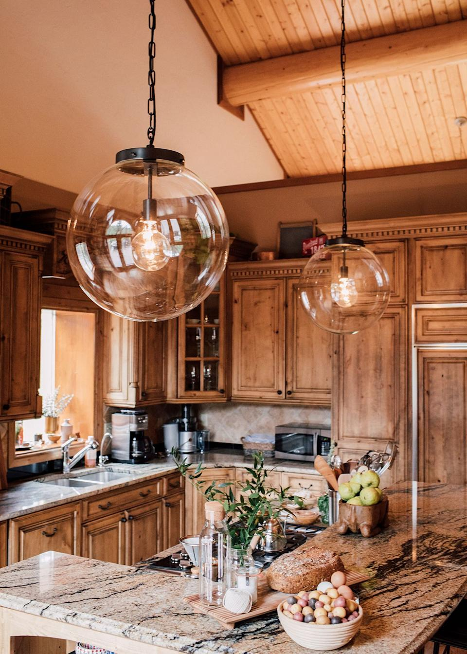 In the kitchen, modern pendant light fixtures meet finely crafted cabinetry and earth-tone marble countertops.