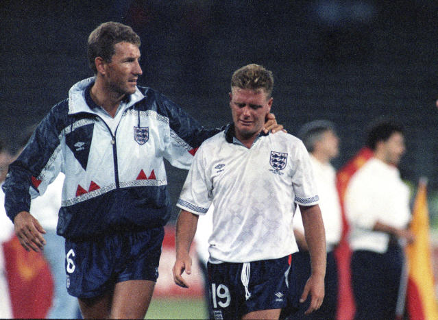 FILE - The July 4, 1990 file photo shows England's Paul Gascoigne crying as he is escorted off the field by team captain Terry Butcher, after England lost a penalty shoot-out in the World Cup semifinal soccer match against West Germany in Turin, Italy. The 21st World Cup begins on Thursday, June 14, 2018, when host Russia takes on Saudi Arabia. (AP Photo/Roberto Pfeil, File)