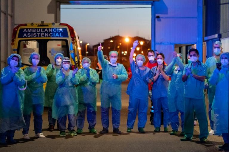 Healthcare workers dealing with the new coronavirus crisis applaud in return as they are cheered on by people outside a hospital in Burgos, Spain