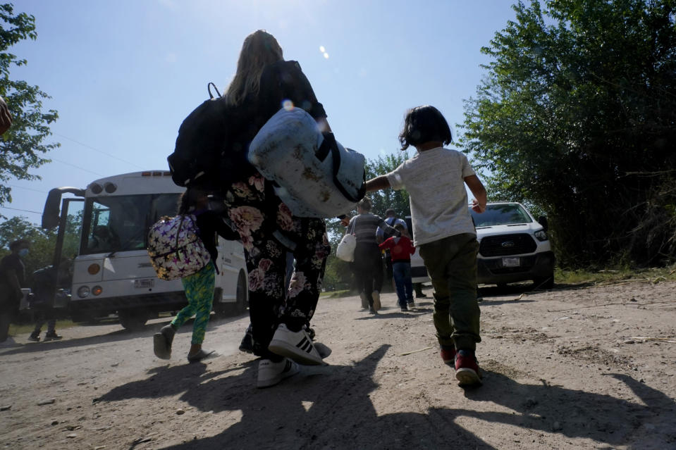 FILE - In this June 16, 2021, file photo, a migrant family from Venezuela move to a Border Patrol transport vehicle after they and other migrants crossed the U.S.-Mexico border and turned themselves in Del Rio, Texas. A Justice Department attorney says the U.S. Centers for Disease Control and Prevention will issue an order this week about treatment of children under a public health order that has prevented migrants from seeking asylum at U.S. borders. (AP Photo/Eric Gay, File)