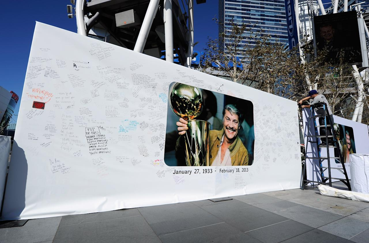 LOS ANGELES, CA - FEBRUARY 20: Workers set up Dr. Buss Memorial Banners in the Nokia Plaza at L.A. Live, directly across the street from Staples Center on February 20, 2013 in Los Angeles, California.  The Lakers will hold a memorial service to celebrate the life of longtime owner Jerry Buss at the Nokia Theater on Thursday, for invited guests only. Dr. Buss died at the age of 80 on Monday following an 18-month battle with cancer.  (Photo by Kevork Djansezian/Getty Images)