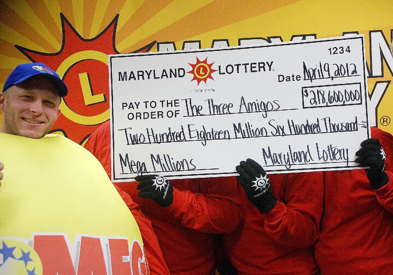 CORRECTS DATE PHOTO WAS MADE TO MONDAY, APRIL 9, NOT TUESDAY, APRIL 10 - In this photo provided by the Maryland State Lottery Agency, a lottery official, left, and the three anonymouswinners of the Maryland portion of the Mega Millions lottery pose for a photo in Baltimore, Monday, April 9, 2012. Maryland Lottery officials say three public school employees are sharing the spoils of the record Mega Millions jackpot. The winning Maryland ticket is one of three nationally that split the $656 million jackpot. (AP Photo/Maryland State Lottery Agency)