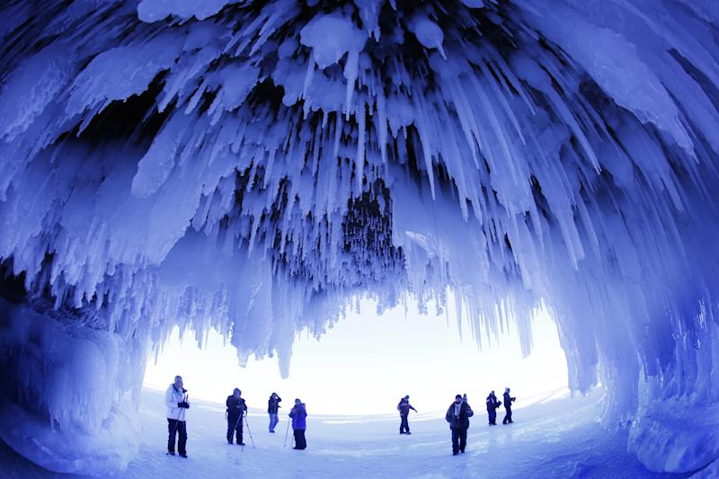 In this Feb. 2, 2014 photo, people visit the caves at Apostle Islands National Lakeshore in northern Wisconsin, transformed into a dazzling display of ice sculptures by the arctic siege gripping the Upper Midwest. The caves are usually accessible only by water, but Lake Superior's rock-solid ice cover is letting people walk to them for the first time since 2009. (AP Photo/Minneapolis Star Tribune, Brian Peterson)
