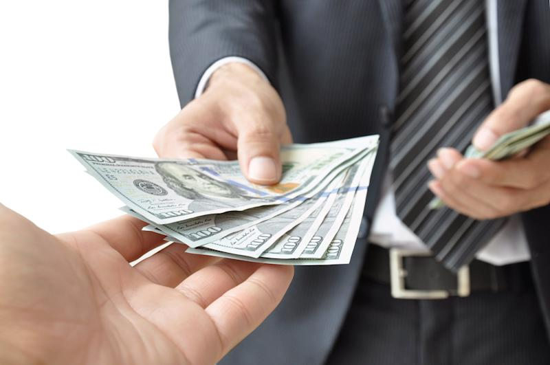 businessman handing another person a stack of hundred-dollar bills.