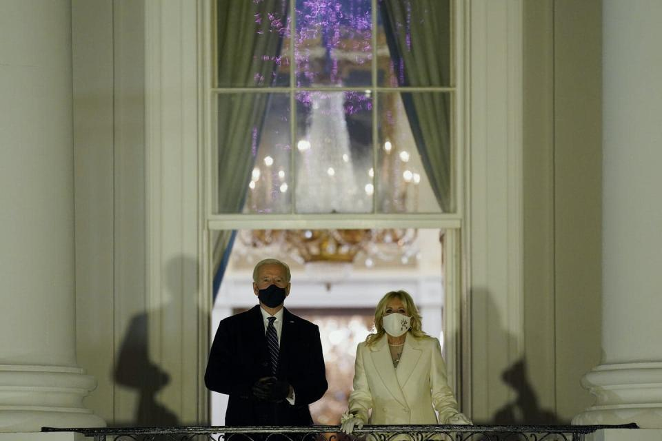 Joe and Jill Biden watch fireworks from a balcony at the White House.
