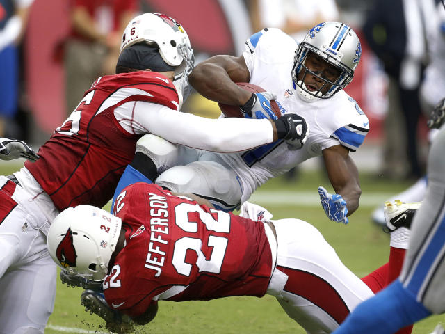 Arizona Cardinals defensive end Ronald Talley (96) loses his helmet as he tackles Detroit Lions running back Reggie Bush (21) as Arizona Cardinals defensive back Tony Jefferson (22) assists during the first half of a NFL football game, Sunday, Sept. 15, 2013, in Glendale, Ariz. (AP Photo/Darryl Webb)