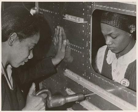 Evelyn T. Gray, Riveter, and Pearlyne Smiley, Bucker, complete a job on the center section of a bomber in this undated handout photo. U.S. National Archives/Handout via REUTERS