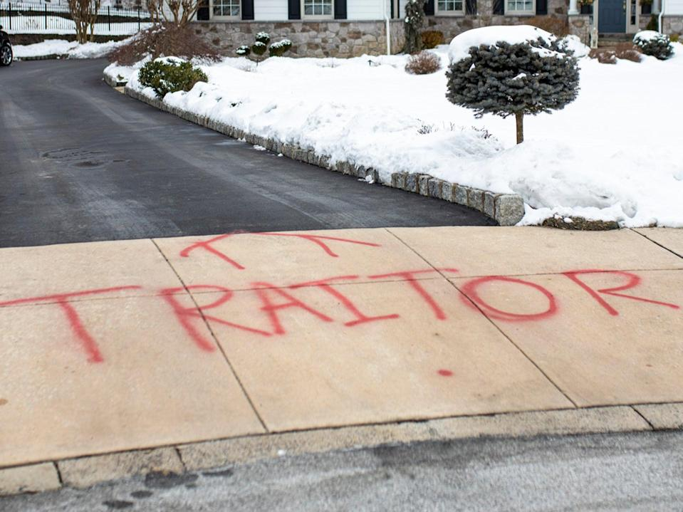 <p>Graffiti is spray painted on the driveway outside of attorney Michael van der Veen's suburban Philadelphia home, Saturday on 13 February 2021</p> ((Associated Press))
