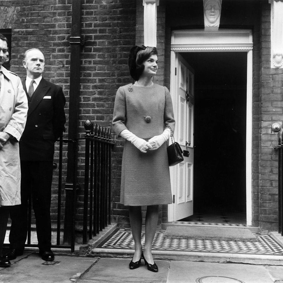 <p>Headed to lunch with Queen Elizabeth II, Jackie is photographed in London wearing a ladylike skirt, gloves, and jacket, adorned with a beautiful brooch.<br></p>