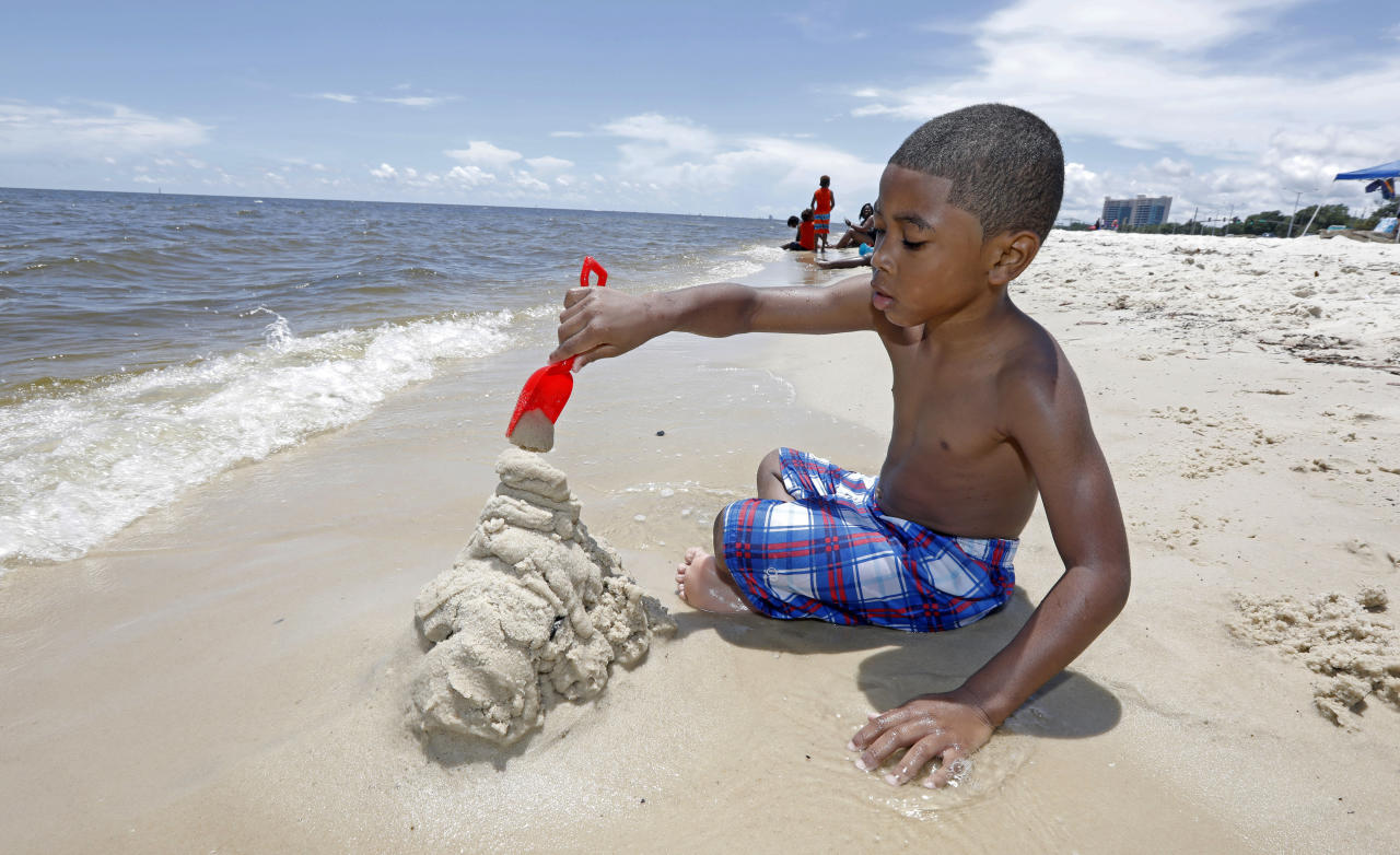 Tyler Ray Wells, 4, builds a sand castle by the water on Biloxi Beach in Biloxi, Miss., Saturday, May 26, 2018, as Subtropical Storm Alberto slowly makes its way through the Gulf of Mexico. The storm is threatening to bring heavy rainfall, storm surges, high wind and flash flooding this holiday weekend. (AP Photo/Rogelio V. Solis)