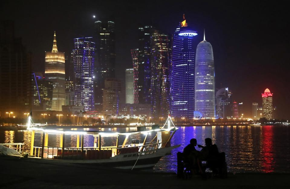 FILE - In this May 14, 2019, file photo, two people talk at the Corniche waterfront promenade in Doha, Qatar. Qataris awoke to a surprise blockade and boycott by Gulf Arab neighbors 3 1/2 years ago, and this week were jolted again by the sudden announcement that it was all over. (AP Photo/Kamran Jebreili, File)