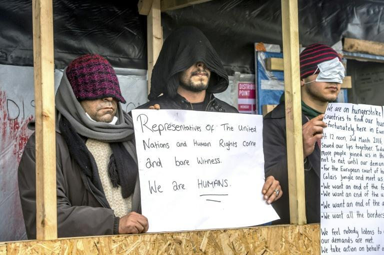 """Iranian migrants who sewed their mouths shut demonstrate against the dismantling of part of the """"Jungle"""" migrant camp in the French northern port city of Calais on March 3, 2016"""