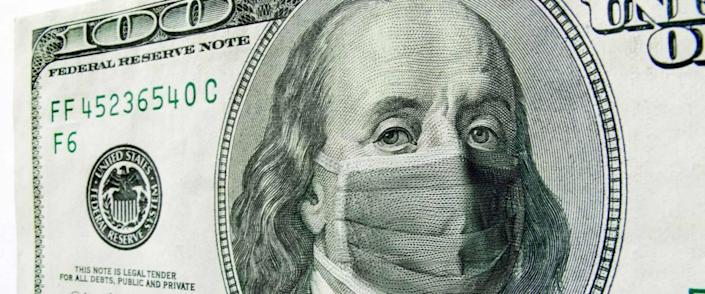 This photo illustration of Ben Franklin wearing a healthcare surgical mask on a one hundred dollar bill.