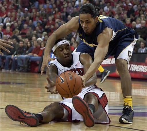 California's Jorge Gutierrez reaches to strip the ball from UNLV's Oscar Bellfield in the first half of an NCAA college basketball game, Friday, Dec. 23, 2011, in Las Vegas. (AP Photo/Julie Jacobson)
