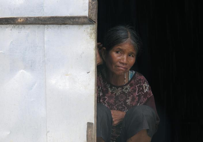 """In this Thursday, Sept. 26, 2013, an elderly woman sits at the door of a """"house church"""" in Kret Krot village in Vietnam's central highlands. Communist Vietnam allows state-sanctioned faiths to grow, but continues to keep a close watch on all religious institutions. In the central highlands, the state believes that small unlicensed churches are often used as a cover for separatist activities. (AP Photo/Chris Brummitt)"""