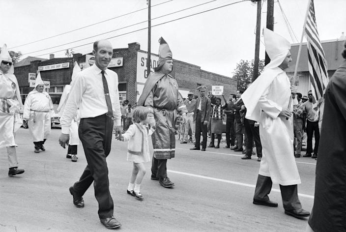 """<span class=""""caption"""">Archival image from 1967 shows protesters demonstrating while Ku Klux Klan members walk in a parade to support the Vietnam War.</span> <span class=""""attribution""""><a class=""""link rapid-noclick-resp"""" href=""""https://www.gettyimages.com/detail/news-photo/young-girl-holding-hands-with-robed-ku-klux-klansmen-walks-news-photo/514694140?adppopup=true"""" rel=""""nofollow noopener"""" target=""""_blank"""" data-ylk=""""slk:Bettmann Archive/Getty Images"""">Bettmann Archive/Getty Images</a></span>"""