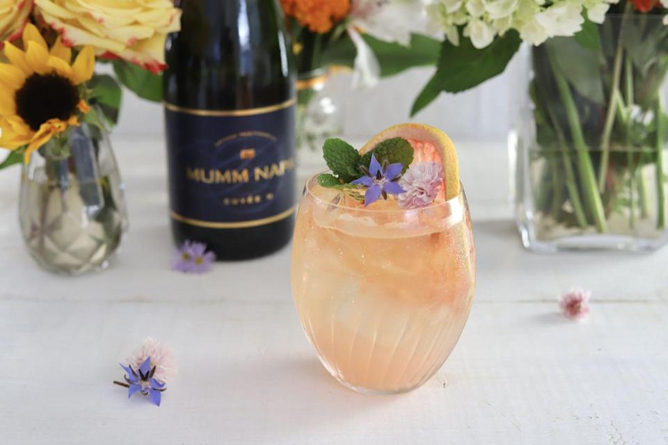 <p>We love this bright and herbaceous take on the effervescent cocktail, and who doesn't love a delicate flower garnish?</p><p><strong>Ingredients:</strong></p><p>3 parts Mumm Napa Cuvée M (or sparkling wine of choice)</p><p>1 part elderflower liqueur (we like St. Germain)</p><p>1 small grapefruit, peeled and chopped </p><p>fresh mint</p><p>club soda</p><p>grapefruit slices and edible flowers, for garnish</p><p><strong>Directions:</strong></p><ol><li>Add 1/2 cup of chopped grapefruit and a few sprigs of fresh mint into a cocktail and muddle. </li><li>Add elderflower liqueur, a splash of club soda, and ice. Shake and strain mixture into a glass, topping off with sparkling wine and garnishing with grapefruit slices and edible flowers.</li></ol>