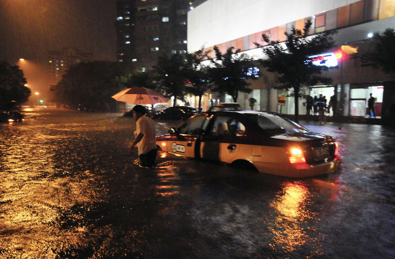 A taxi driver walks away after his car was stranded in a flooded street following a heavy rain in Beijing Saturday, July 21, 2012. China's government says the heaviest rains to hit Beijing in six decades. The torrential downpour Saturday night left low-lying streets flooded and knocked down trees. (AP Photo) CHINA OUT