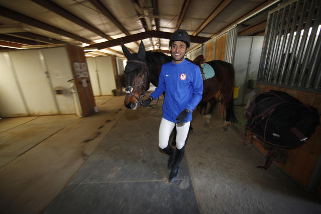 USA Olympic modern pentathlon team member Amro ElGeziry leads his horse, Chino, to practice at a stable in Fountain, Colo., Friday, April 24, 2020. (AP Photo/David Zalubowski)