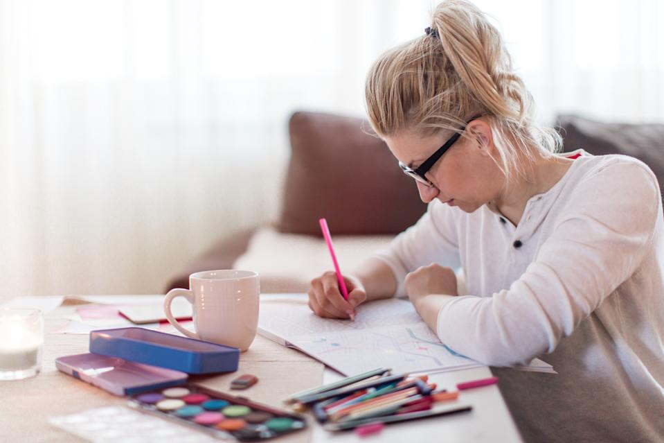 Young woman is relaxing at home and drawing in colouring book for adults