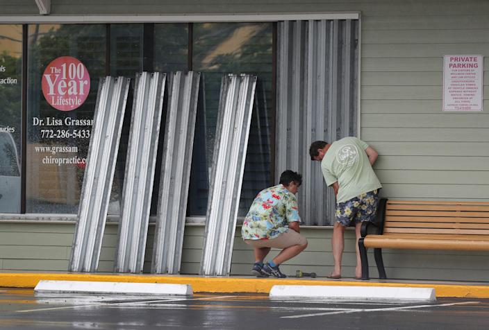 Donald Bowen, left, and Doug Smith put shutters over the windows of their business as Tropical Storm Isaias approaches in Stuart, Fla., on Aug. 1, 2020. (Joe Raedle / Getty Images)