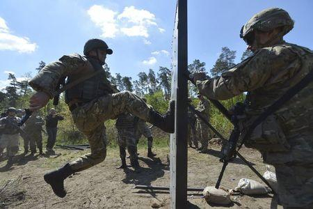 """A serviceman of the U.S. Army's 173rd Airborne Brigade Combat Team (R) trains Ukrainian soldiers during a joint military exercise called """"Fearless Guardian 2015"""" at the military training area in Yavoriv, outside Lviv, Ukraine, May 12, 2015. REUTERS/Oleksandr Klymenko"""