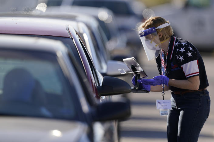 FILE - In this Tuesday, Nov. 3, 2020 file photo, an election worker instructs a voter at a drive-through polling location in Kansas City, Mo. The location was established to provide access for people who have tested positive for COVID-19 and elderly voters. (AP Photo/Charlie Riedel)