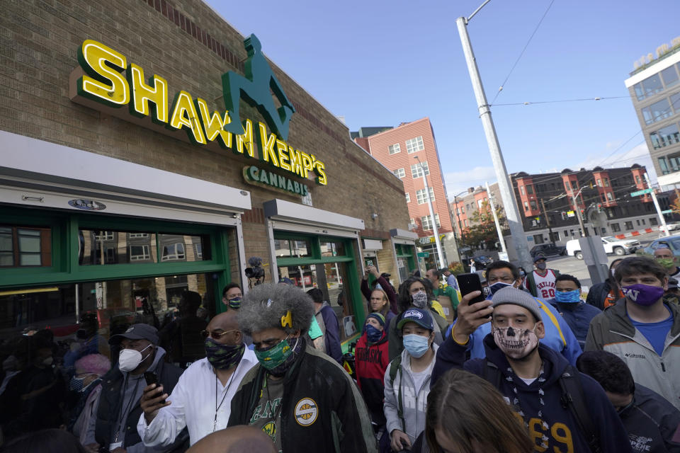 Fans and customers wait outside Shawn Kemp's Cannabis, the marijuana dispensary owned by Shawn Kemp, a former NBA basketball player for the Seattle SuperSonics and several other teams, and other business partners, Friday, Oct. 30, 2020, prior to the store's grand opening in downtown Seattle. (AP Photo/Ted S. Warren)