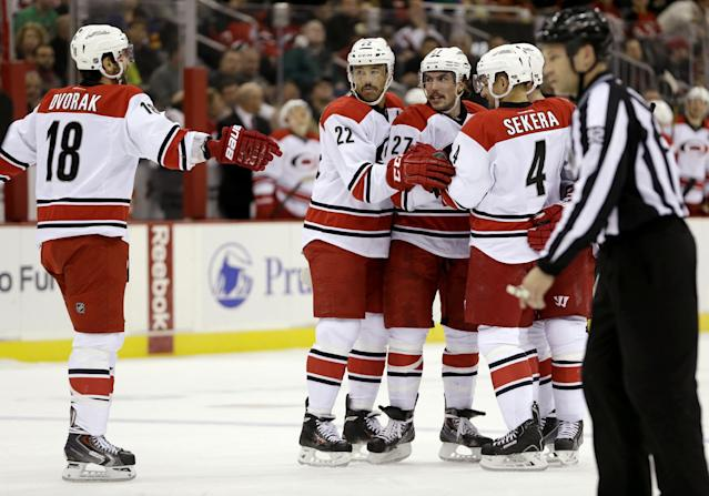 Members of the Carolina Hurricanes celebrate a goal by defenseman Justin Faulk (27) during the first period of an NHL hockey game against the New Jersey Devils, Wednesday, Nov. 27, 2013, in Newark, N.J. (AP Photo/Julio Cortez)