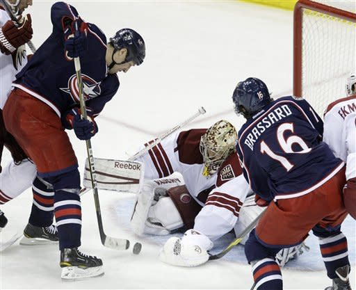 Phoenix Coyotes' Jason LaBarbera, center, makes a save between Columbus Blue Jackets' R.J. Umberger, left, and Derick Brassard (16) during the third period of an NHL hockey game on Tuesday, March 6, 2012, in Columbus, Ohio. The Blue Jackets beat the Coyotes 3-2. (AP Photo/Jay LaPrete)